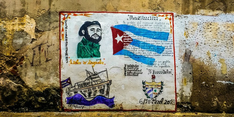 A mural propped up against a delapidated wall in Cuba