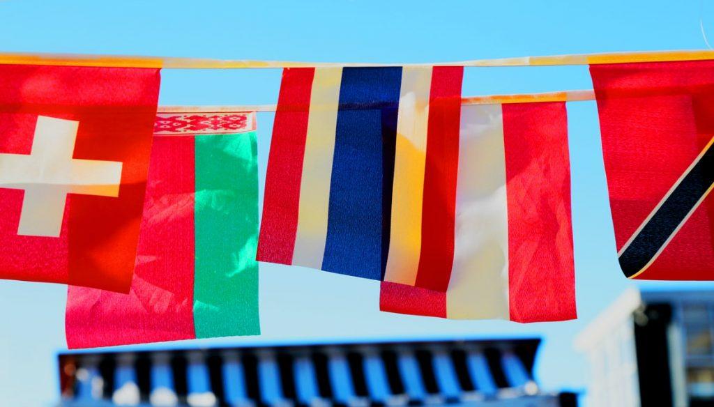 coloured flags hang on a row outside