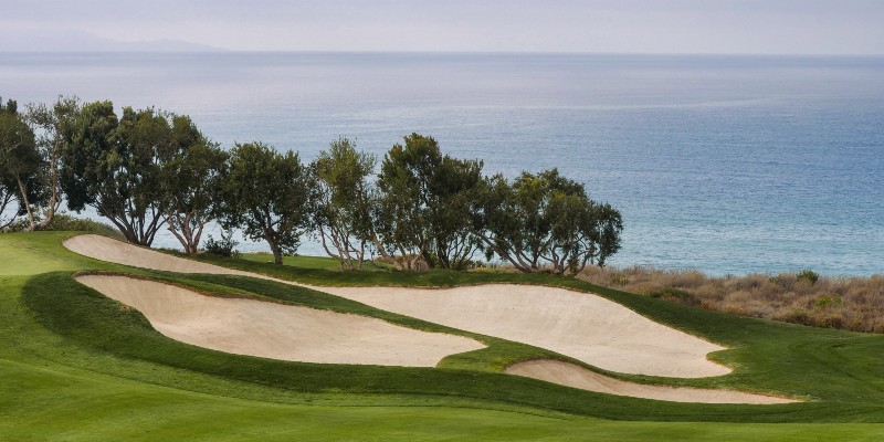 View from a golf course with sand dunes and ocean background