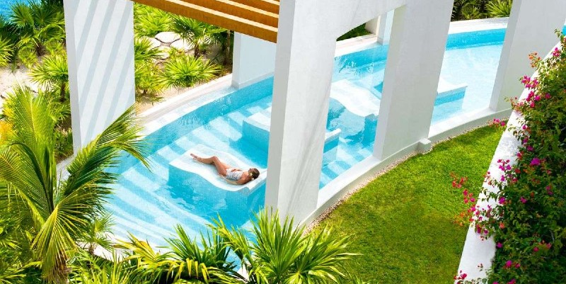 Woman relaxing in the pool at Excellence Playa Mujeres