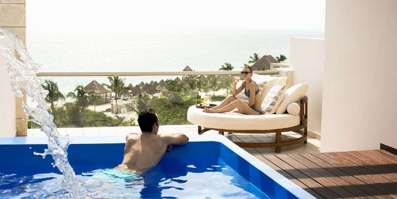 Man and woman relax on the balcony of their room at Excellence Playa Mujeres