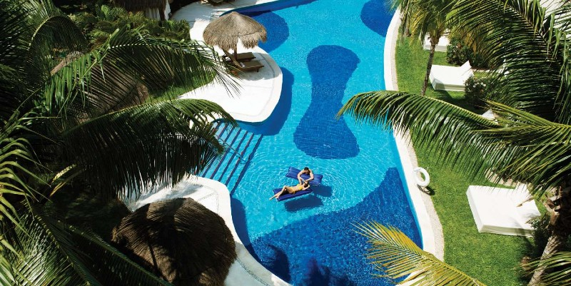 Two people lounge on an inflatable in the pool at Excellence Riviera Cancún