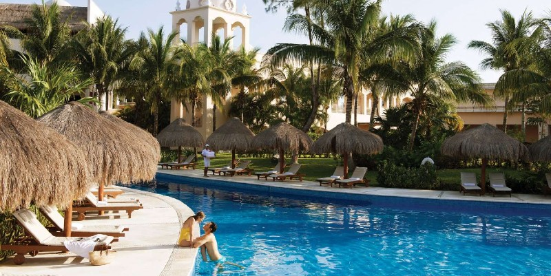Two people relax in the pool at Excellence Riviera Cancún