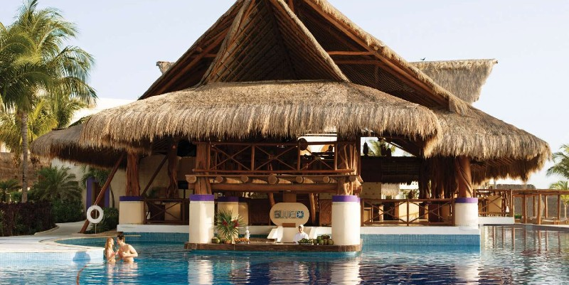 Two people relax in the pool in front of Blue Swim-Up Bar at Excellence Riviera Cancún