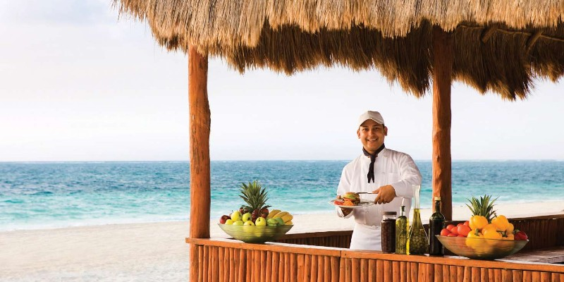 Beach bar man waits to take an order with the sand and sea in the background at Excellence Riviera Cancún