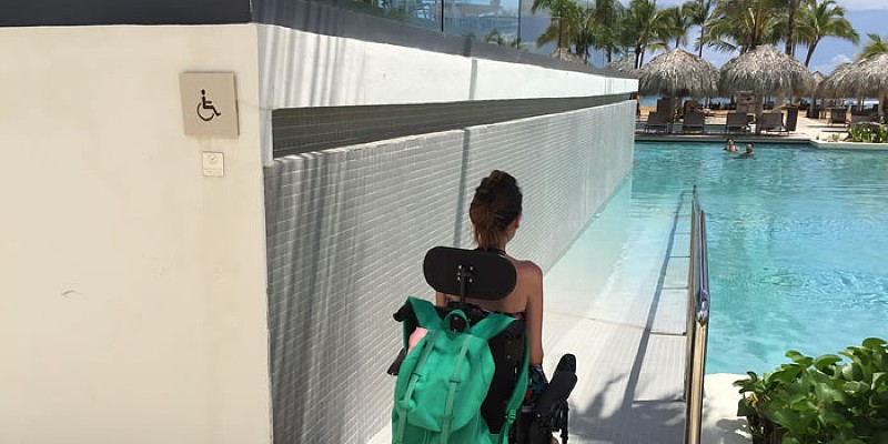 A woman in a wheelchair makes her way down the ramp to an outdoor swimming pool at a resort in Dominican Republic