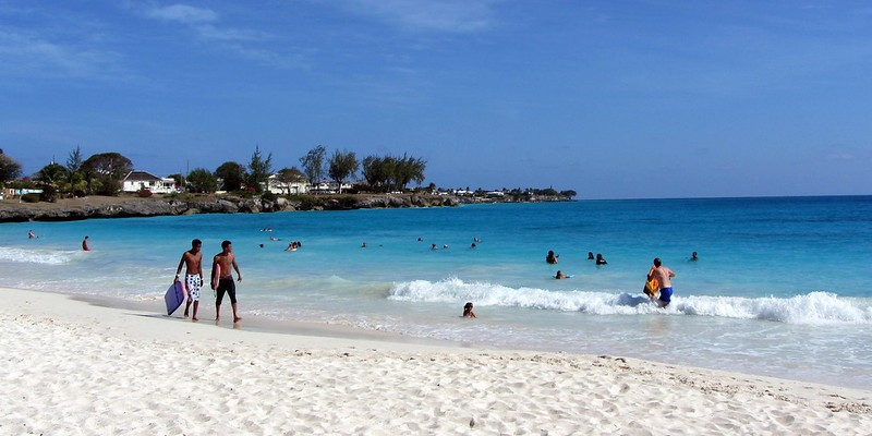 People walk on the sand and play in the sea at Miami (or Enterprise) Beach in Oistins, Barbados.