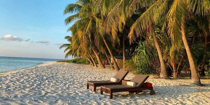 Two sun loungers next to each other on a tropical beach