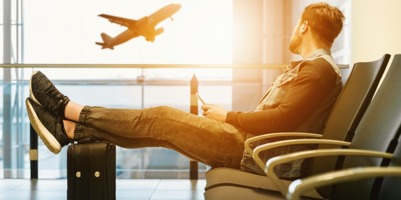 Man sitting in an airport looking out the window at a plane taking off