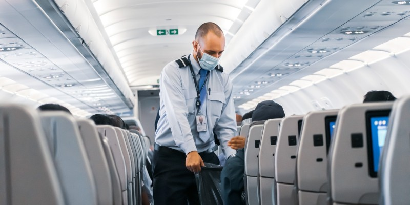Flight attendant collecting litter on a plane with a face covering on