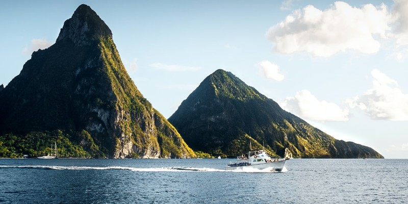 A boat sailing in the water in front of the Pitons in St Lucia