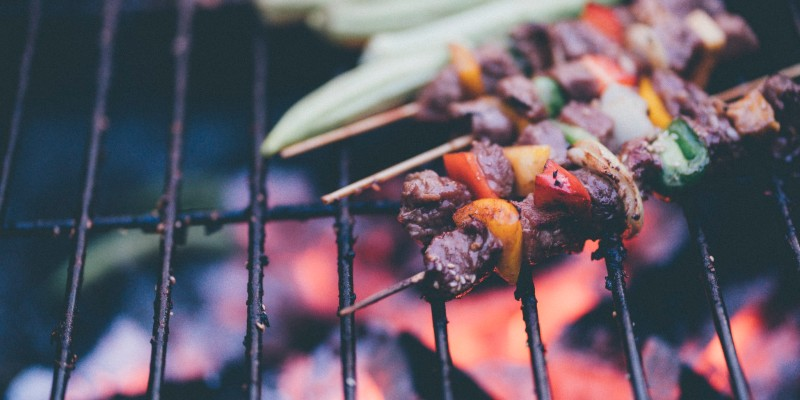Kebabs cook on a barbeque grill over open flames