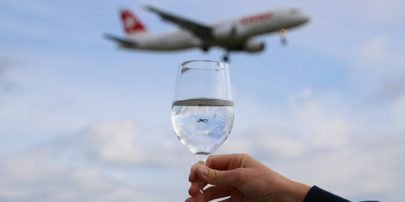 a person holding a glass of liquid with a plane flying in the distance