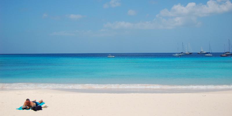 A man sunbathing on a Barbados beach